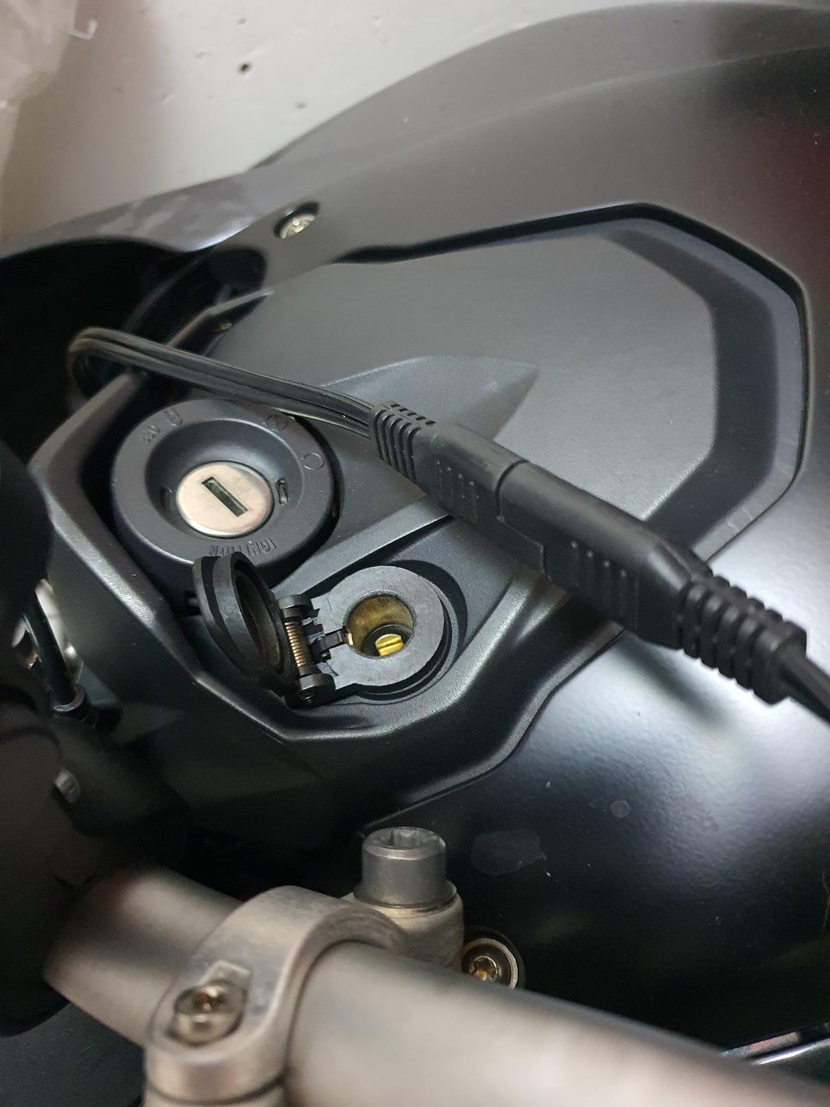 Una BMW GS con il cavetto ad occhielli fissato direttamente alla batteria: nessuna noia con il sistema can-bus che gestisce la presa DIN (visibile in basso, aperta)